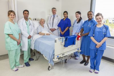 20705719 - senior female woman patient in hospital bed surrounded by the multi ethnic interracial medical team of men and women male and female doctors and nurses